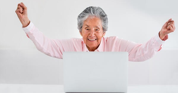 Elder woman celebrating over 50 looking at her social media accounts